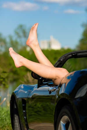 cabrio: Young woman hanging her legs over the door of her cabriolet