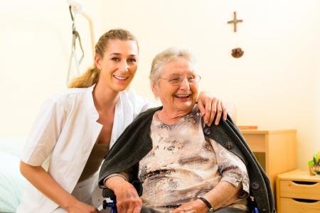 enfermeros: Enfermera joven y mujer mayor en hogar de ancianos, la anciana sentada en una silla de ruedas