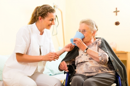 geriatric care: Young nurse and female senior in nursing home, the old lady sitting in a wheel chair Stock Photo