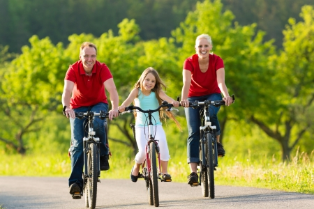 Family with one girl having a weekend excursion on their bikes or bicycles on a summer day in beautiful landscape photo