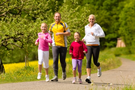 young woman running: Happy Family with two girls running or jogging for sport and better fitness in a meadow in summer