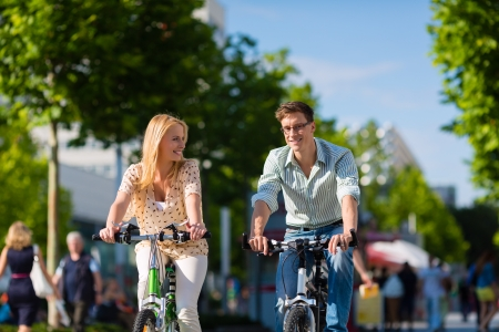 weekend activities: Couple - man and woman - riding their bikes or bicycles in their free time and having fun on a sunny summer day