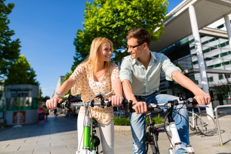 free time: Couple - man and woman - riding their bikes or bicycles in their free time and having fun on a sunny summer day