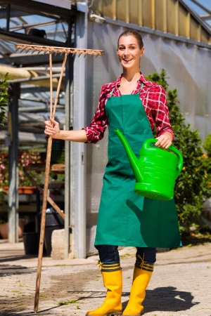 watering pot: Female commercial gardener in front of green house with watering pot and rake