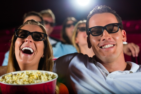 young people watching 3d movie at movie theater photo