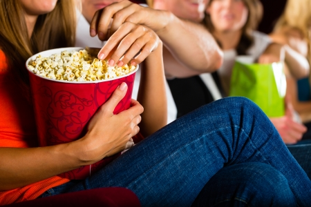 funny movies: Woman eating large container of popcorn in cinema or movie theater Stock Photo