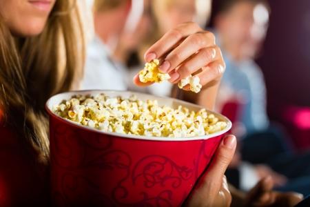 Mujer comiendo gran contenedor de palomitas en el cine teatro o una película Foto de archivo