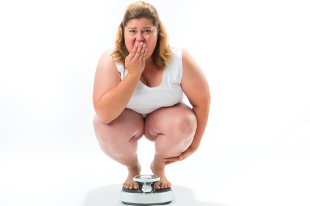 losing control: Diet and weight, obese young woman crouching on a scale measuring her weight