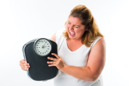 reduction: obese woman looking pissed or angry at scale