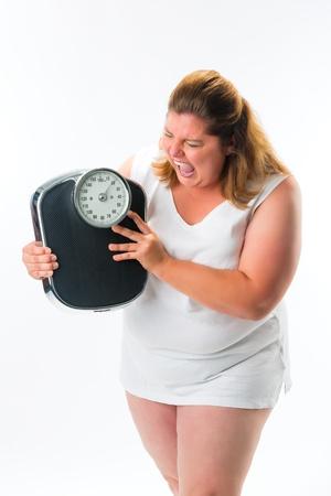 obesidad: mujer obesa mirando molesto o enojado con escala Foto de archivo