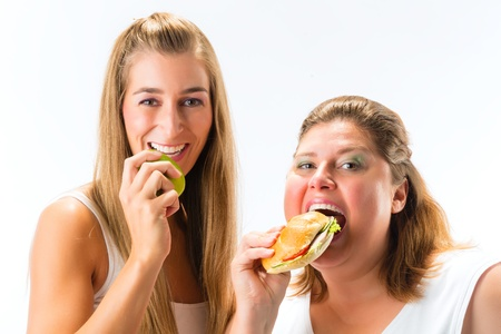 fat and slim: Healthy against unhealthy - Thin and fat woman eating an apple and sandwich