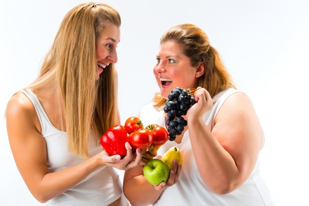 fat and slim: Healthy eating - happy women of different size with fruits and vegetables