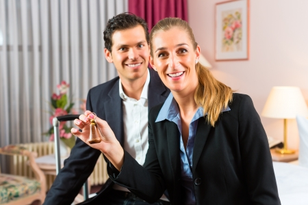 Young couple sitting on the bed in the hotel room and the woman has a key in her hand Stock Photo - 17657339