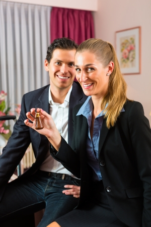 Young couple sitting on the bed in the hotel room and the woman has a key in her hand Stock Photo - 17657340