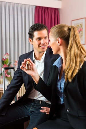 Young couple sitting on the bed in the hotel room and the woman has a key in her hand Stock Photo - 17657307