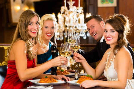 Good friends for dinner or lunch in a fine restaurant, clinking glasses Stock Photo - 17657316