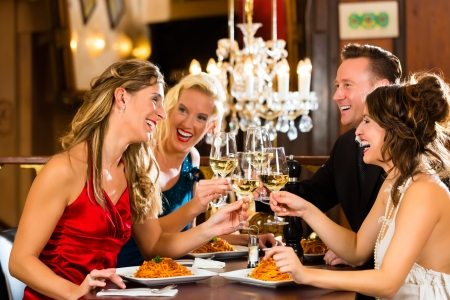 Good friends for dinner or lunch in a fine restaurant, clinking glasses Stock Photo - 17657251
