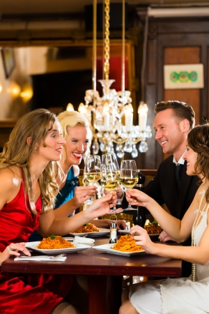 Good friends for dinner or lunch in a fine restaurant, clinking glasses Stock Photo - 17657282