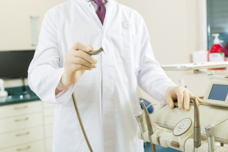 Dentists in his surgery holds a drill and looking at the viewer, in the background are tools for a dentist Stock Photo - 17657377