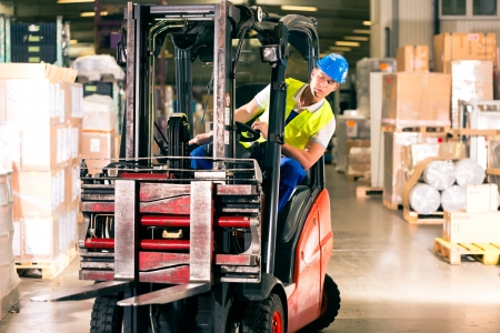 forklift driver: forklift driver in protective vest driving forklift at warehouse of freight forwarding company