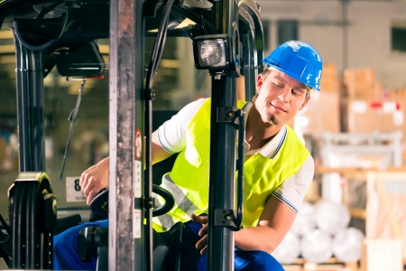 forklift driver in protective vest driving forklift at warehouse of freight forwarding company Stock Photo - 17657320