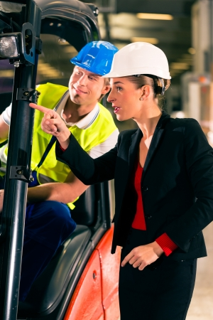 Forklift driver at warehouse of freight forwarding company, female super visor or coworker, pointing photo