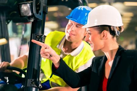 forwarding: Carretilla elevadora conductor en el almac�n de la empresa de transporte de carga, hembra visera super o compa�ero de trabajo, se�alando