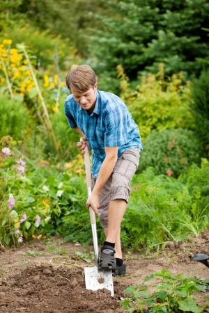 gardener digging the soil with a spade to make the garden ready