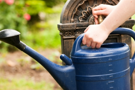 woman only: Garden scene - woman, only hands to be seen, refilling the watering pot at a tap