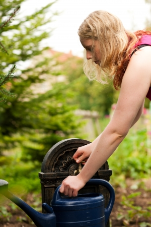 refilling: Garden scene - woman refilling the watering pot at a tap