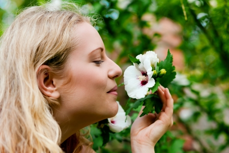 Very beautiful Woman in her garden taking a sniff at some flowers Stock Photo - 17743350