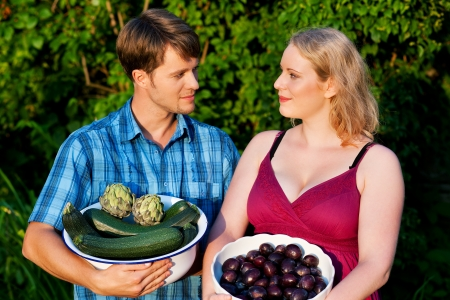 gardeners or farmers presenting zucchini, artichokes and plums from the harvest  photo
