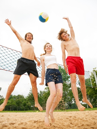 overly: Group of three friends - one woman and two men - playing beach volleyball, the day is not overly sunny but they do not care and have fun nevertheless Stock Photo