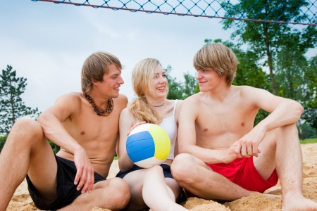 ballgame: Group of three friends - one woman and two men - playing beach volleyball, the day is not overly sunny but they do not care and have fun nevertheless Stock Photo