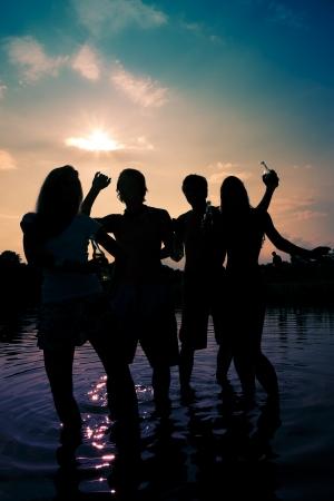 fiesta amigos: Las personas dos parejas en la playa bailando a la m�sica, beber y tener un mont�n de diversi�n en el sol s�lo la silueta de la gente por ver, las personas que tienen las botellas en sus manos Foto de archivo
