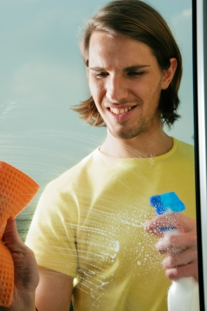 houseman: Young man cleaning his windows with spray and sponge Stock Photo