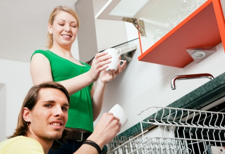 Couple emptying the dishwasher and sorting the dishes in a kitchen cupboard photo
