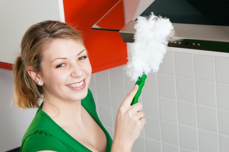 apartment cleaning: Woman dusting her apartment using a duster