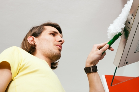 dusting: Man doing chores dusting his apartment using a duster
