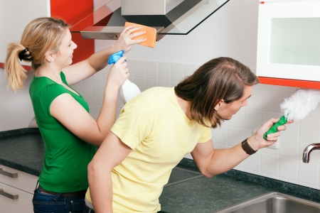 Young couple cleaning their apartment after moving in together photo