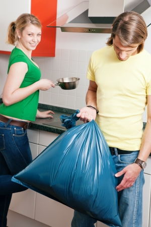 Young couple doing chores and cleaning the apartment, he is not too happy to have to get out the garbage weaseling out of the task photo