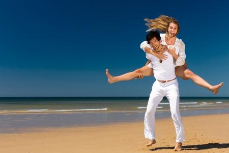Pareja juguetona en la playa del océano disfrutando de sus vacaciones de verano, el hombre está llevando a cuestas la mujer