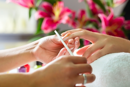 Woman in a nail salon receiving a manicure by a beautician Stock Photo