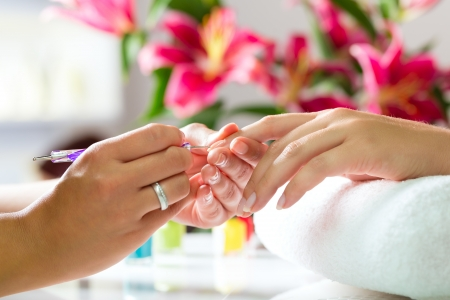 polishing: Woman in a nail salon receiving a manicure by a beautician Stock Photo