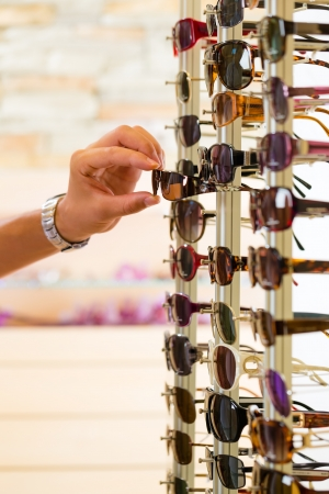 optician: Young man (only hands) at optician with glasses, he might be customer or salesperson and is looking for sunglasses