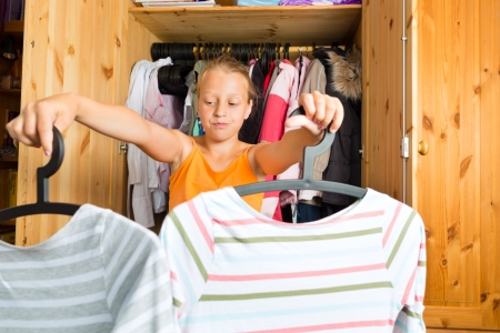 stumped: Family - child or teenager in front of her closet or wardrobe and looking for outfit Stock Photo