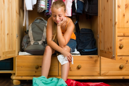 adolescence: Family - child or teenager in front of her closet or wardrobe and looking for outfit Stock Photo