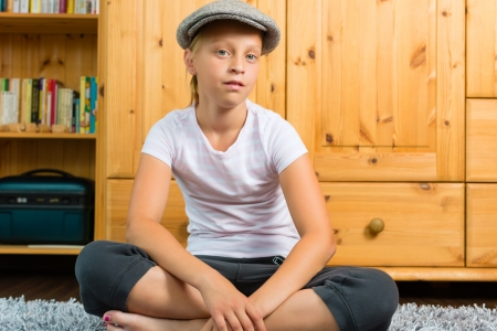 Family - child or teenager sitting with cap in room on the floor Stock Photo - 17798438