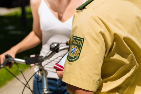 public sector: Police - young woman on bicycle with police officer in traffic control