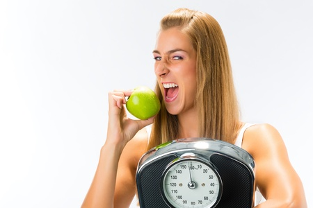 ideal: Diet and weight, young woman with scale under her arm and apple